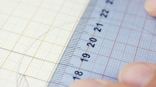 Person measuring accurate on the graph paper, using ruler and pencil, close-up