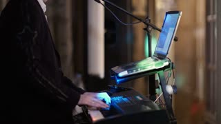 Person playing an electronic keyboard with bright party lights, close up view of the hands