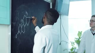 Pharmacy lab worker, medical or chemistry student at chalkboard writing organic chemistry formula, while teacher or colleague is helping