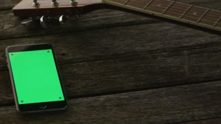 Phone with Green Screen in Portrait Mode Laying on Wooden Table next to Guitar and Headphones. Causal Lifestyle