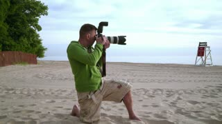 Photographer takes photo on sea beach. Photographer working with professional camera. Photographer in action. Professional photographer outdoor. Photographer shooting photo session