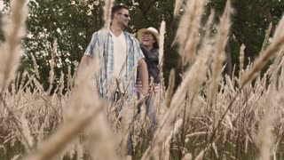 Piggyback. Casually dressed heterosexual in-love couple having fun together in field. Steadicam shot.