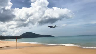 Plane approaching for landing and passing just above the camera at the beach