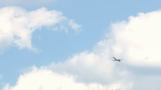 Plane Flying Across Partly Cloudy Skies