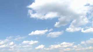 Plane Flying Across Partly Cloudy Sky