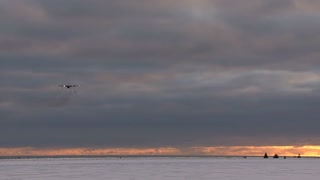 Plane Flying Over Ice At Sunset