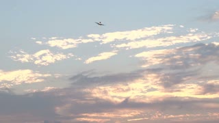 Plane Flying Through Colorful Bermuda Sky At Sunset