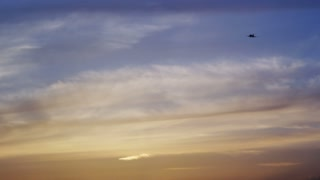 Plane Flying Through Sunset Sky Above