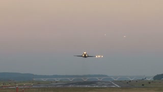 Planes Taking Off and Landing in Early Night Sky
