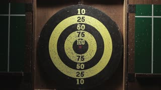 Playing darts on an old used dart board.