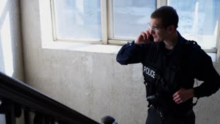 Police Officer On Smart Phone In Sketchy Stairwell Of Building