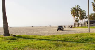 Police SUV and Bicyclists on California Beach