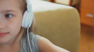 Portrait blonde girl 8 years listening music in headphones and looking and smiling at camera. Zooming