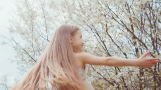 Portrait girl 7 years old spinning in a dress on a background of blooming trees. Slow Motion Sony A6300
