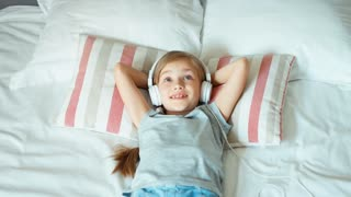 Portrait girl child listening music in headphones and lying on the bed. Zooming