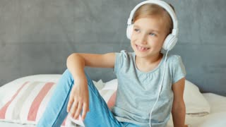 Portrait laughing girl listening music in white headphones. Zooming