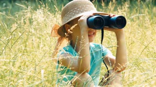 Portrait laughing young naturalist through binoculars watching wildlife. Child sitting in the high grass. Zooming