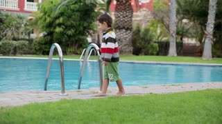 Portrait of a little boy walking beside swimming pool