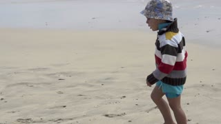 Portrait of a little boy walking on the beach, slow motion shot at 240fps