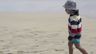 Portrait of a little boy walking on the beach, slow motion shot at 60fps