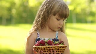 Portrait of a smiling child with a basket of strawberries