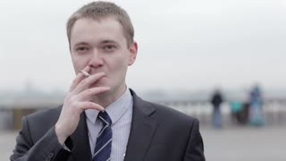 Portrait of a young Caucasian businessman wearing a formal elegant gray suit, thinking while smoking a cigarette outdoors