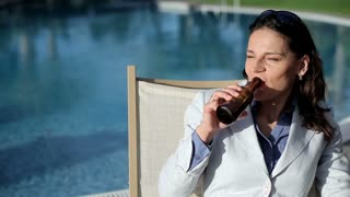Portrait of beautiful businesswoman drinking beer by the poolsde