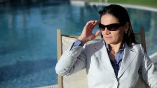 Portrait of beautiful businesswoman resting by the poolsde