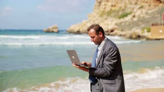 Portrait of businessman finishing work on laptop and of smiling on the beach