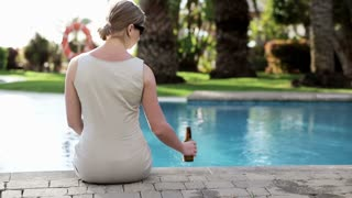 Portrait of businesswoman drinking beer by the poolsde