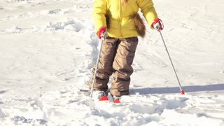 Portrait of child, girl is making first steps on skis