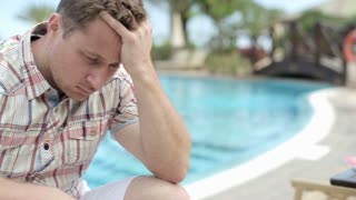 Portrait of sad man sitting by the swimming pool, steadycam shot