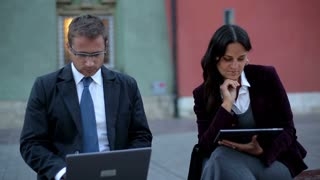 Portrait of smiling business people with laptop and tablet computer, outdoors