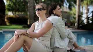 Portrait of smiling businesswoman resting by the poolsde with friend