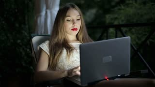 Portrait of smiling woman with laptop sitting on her balcony in the evening
