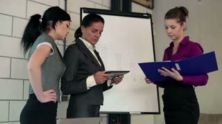Portrait of three serious looking businesswoman with flipchart
