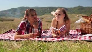 Portrait of two girlfriends drinking wine on picnic, crane shot