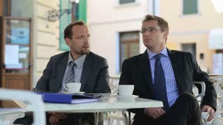 Portrait of two smiling businessmen on meeting in cafe outside
