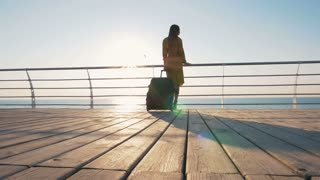 Portrait of young attractive woman in sunglasses at seafront, dolly shot, slow motion