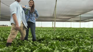 Portrait of young happy proud farming couple on there lettuce farm.