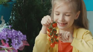 Portrait smiling girl holding bunch of cherry tomatoes and smiling at camera. Thumb up. Ok. Zooming