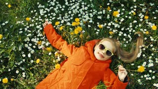 Portrait smiling girl lying in the grass and looking at the camera. Girl in a red coat and sunglasses. Girl holding flowers in her hand. Panning. Zooming