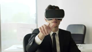 Portraite Young businessman wearing virtual reality headsets in white future white office. He clicks his fingers in the air and turns his head