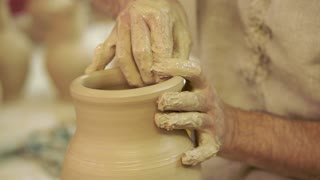 Potter works. Crockery creation process in pottery on potters' wheel