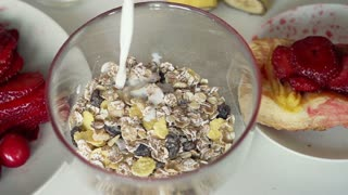 Pouring milk into bowl with muesli