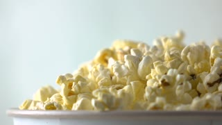Pouring popcorn into paper box. Cinema or fast food concepts. Super slow motion dolly video