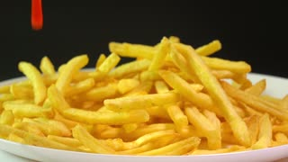 Pouring tomato sauce over french fries. Popular fast food, deep fried potato chips. Super slow motion video