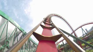 POV Shot of Twisting Red and Yellow Roller Coaster