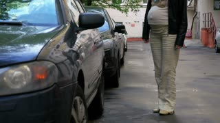 Pregnant woman getting into a car parked in the yard and taking drivers seat. She is going to travel alone