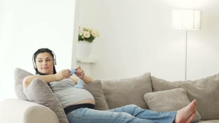 Pregnant woman listening to music in headphones and holding baby booties